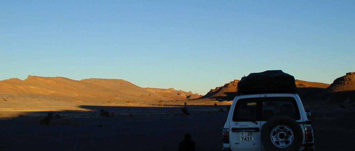 The Hamar Laghdad in the evening Sun is on the back. The Kess-Kess mud mounds are also faintly visible near the horizon.